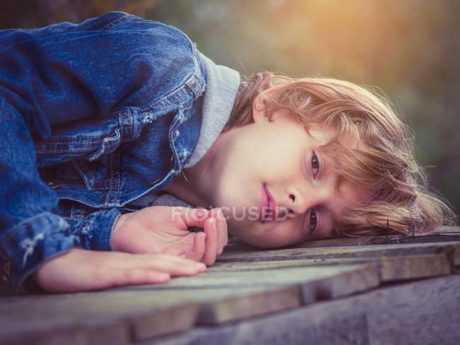 Boy lying on board — Stock Photo