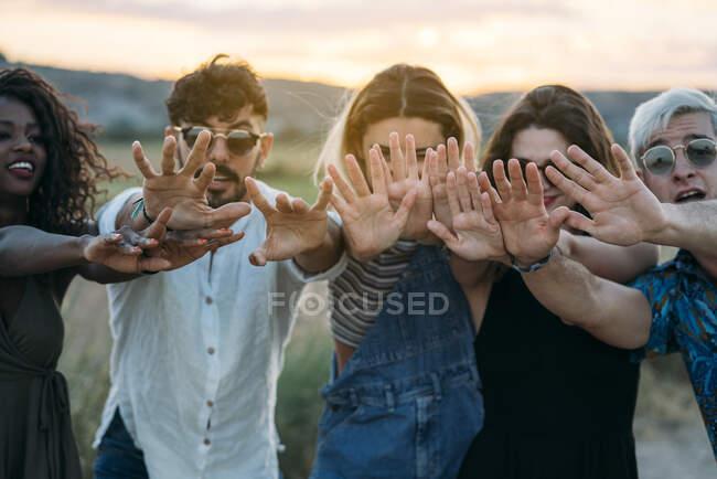 Grupo de diversos jóvenes amigos sonriendo y extendiendo las manos hacia la cámara mientras están de pie sobre un fondo borroso de un paisaje increíble durante la puesta del sol - foto de stock