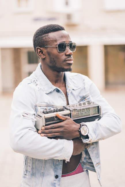 Продуманий чорна людина в сонцезахисні окуляри, проведення vintage радіо пристрій — стокове фото