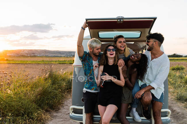 Group of cheerful young people standing near retro van and laughing while spending time in nature together — Stock Photo