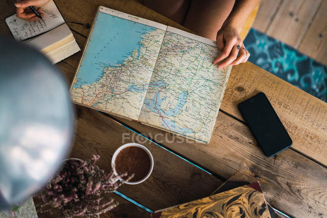 Hands of woman woman with map on wooden table, planning trip — Stock Photo