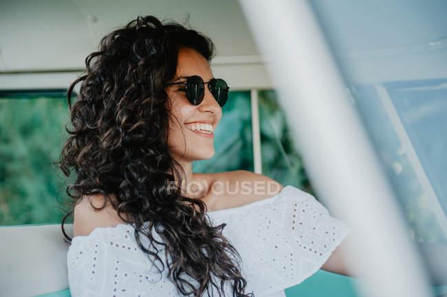 Sonriente morena joven mujer sentado dentro de coche - foto de stock