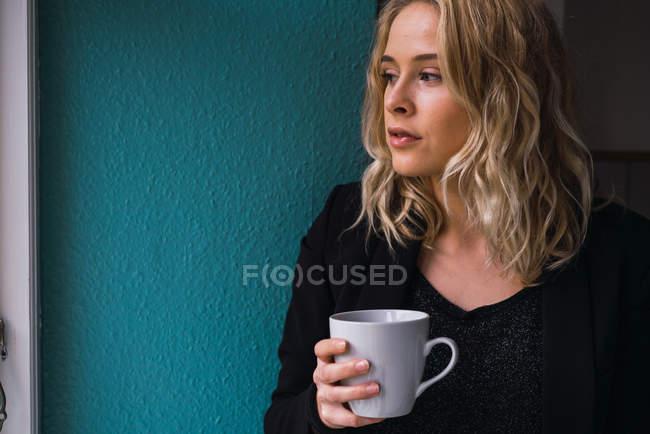 Ritratto di giovane donna bionda in piedi con una tazza di caffè a casa — Foto stock