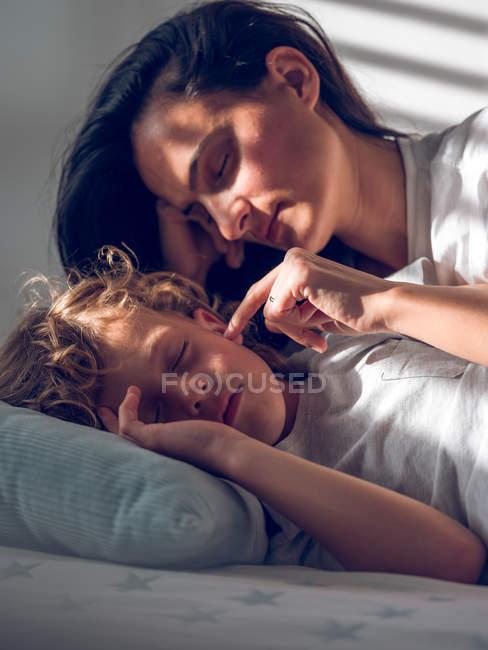 Красивая женщина лежит на кровати за сладким мальчиком и осторожно касается его щеки. — стоковое фото