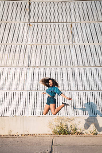 Funky young African American woman with dark hair in denim clothes and sneakers jumping high on street against wall — Stock Photo