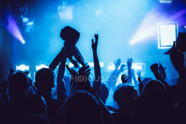 Anonymous people holding hands up and cheering while spending time on amazing music show — Stock Photo