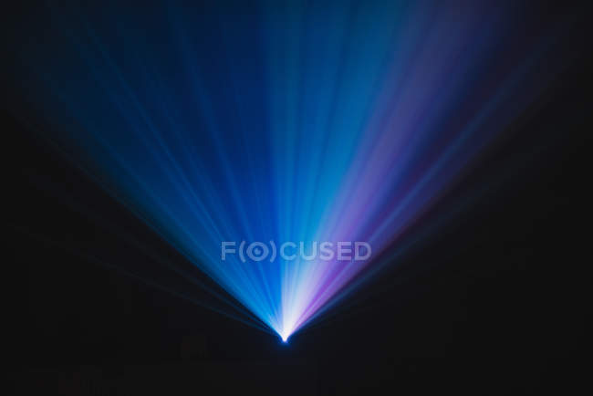 Blue and violet beams of bright laser light shining on black background — Stock Photo