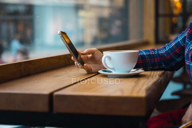 Femme assise dans un café avec une tasse de café — Photo de stock