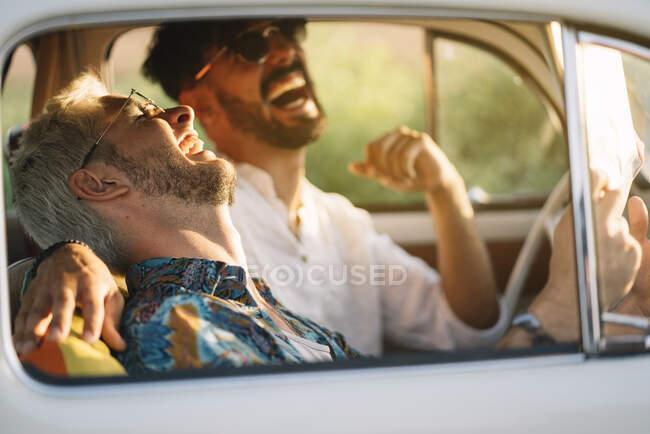 Два молодых парня смеются и держат карту, сидя в ретро-машине во время приятного путешествия — стоковое фото