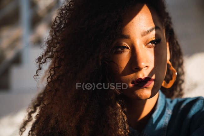 Young thoughtful African American woman with curly hair and vivid makeup looking away with shadow on face — Stock Photo