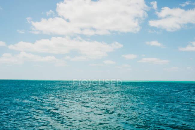 Облака над волнами моря — стоковое фото