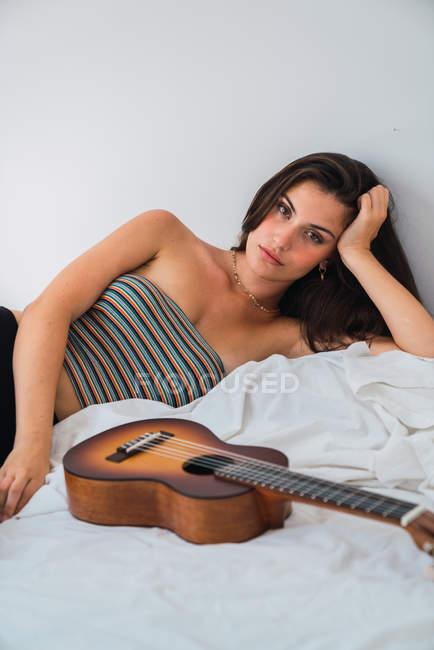 Молода брюнетка жінка лежить на ліжку з ukulele і, дивлячись на камеру — стокове фото