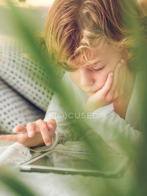Нудно хлопчик тикати цифровий планшетний екран лежачи на зручні дивани — стокове фото