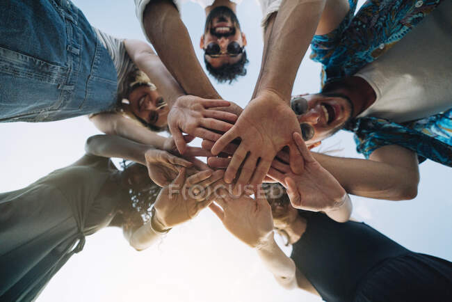From below shot of young friends laughing and holding hands together while standing on background of clear sky — Stock Photo