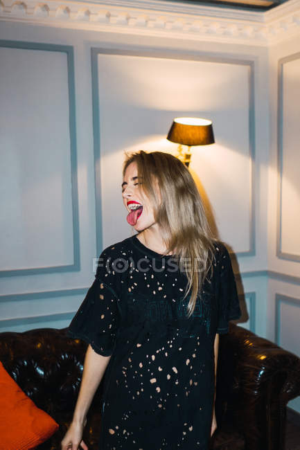 Blonde funky woman with tongue out posing in room — Stock Photo