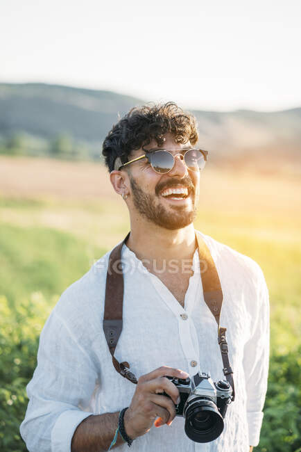 Handsome young guy in sunglasses cheerfully smiling and holding retro photo camera while standing on blurred background of amazing countryside — Stock Photo