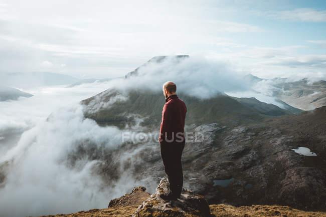 Турист стоит на краю горы и смотрит на вид на острова Фероэ — стоковое фото