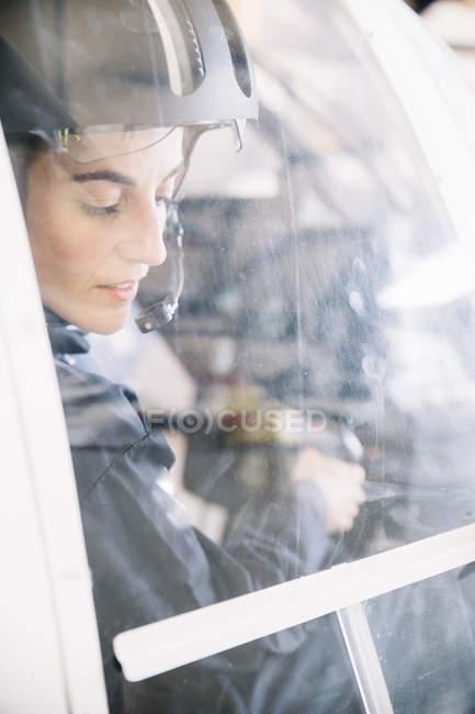 Gros plan de femme pilote assis en hélicoptère et en regardant vers le bas derrière la fenêtre — Photo de stock