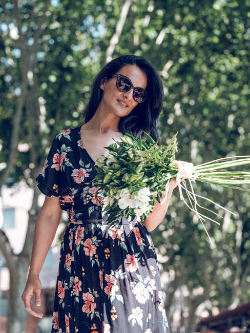 Attractive woman with bunch of flowers — Stock Photo