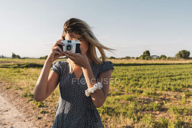Woman in dress taking photo with retro camera standing on background of green summer landscape in sunlight — Stock Photo