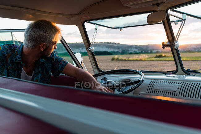 Handsome young man leaning on steering wheel of retro car and looking away while traveling in nature — Stock Photo