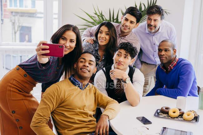 Multiracial equipe de pé e sentado enquanto tomar selfie na mesa no escritório. — Fotografia de Stock