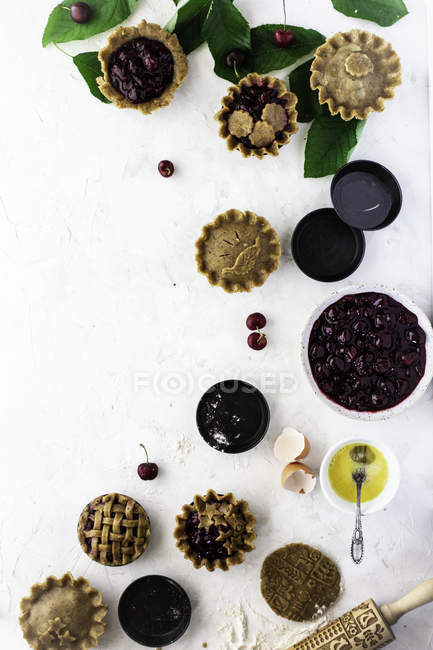 Assortment of tartlets with berry stuffing and cooking ingredients on white background — Stock Photo
