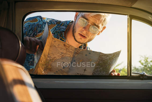 Bello giovanotto con mappa sorridente e guardando dentro auto d'epoca mentre viaggia in campagna — Foto stock