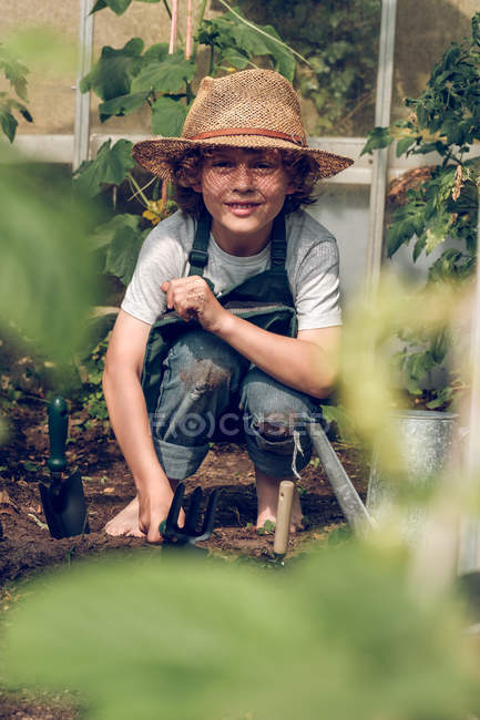 Boy working in greenhouse — Stock Photo