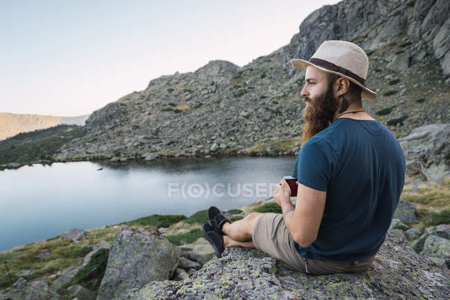 Young relaxed man in hat sitting on rocks near lake in mountains — Stock Photo