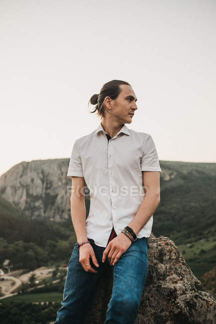 Handsome young guy sitting on rock and looking away while spending time in nature — Stock Photo