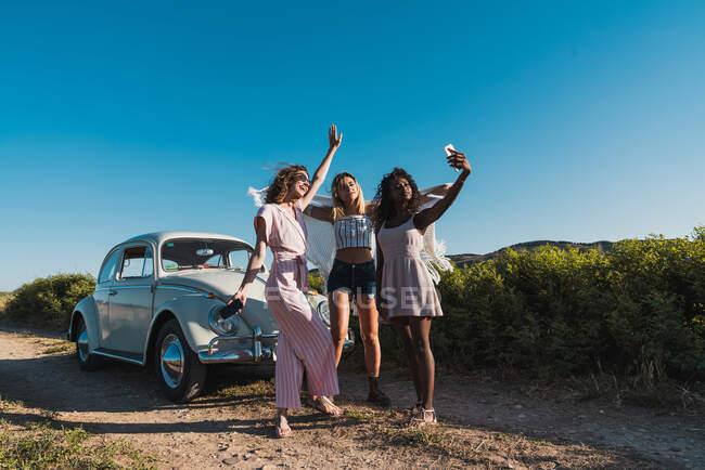 Стильные мультиэтнические женщины делают селфи со смартфоном на сельской дороге с винтажным автомобилем на фоне голубого неба — стоковое фото