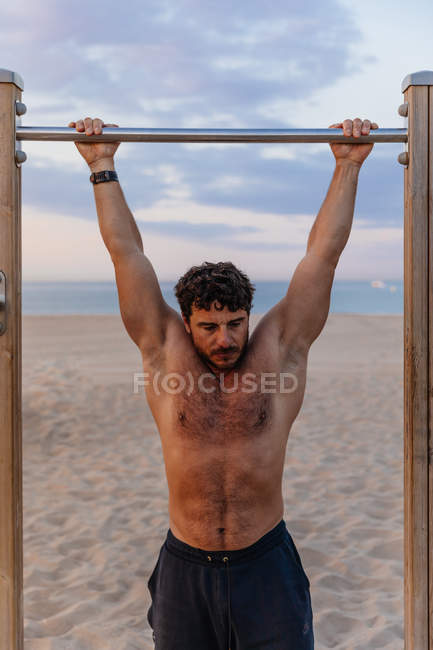 Musculoso chico realizar pull-ups en bar durante la puesta del sol en la playa de arena - foto de stock