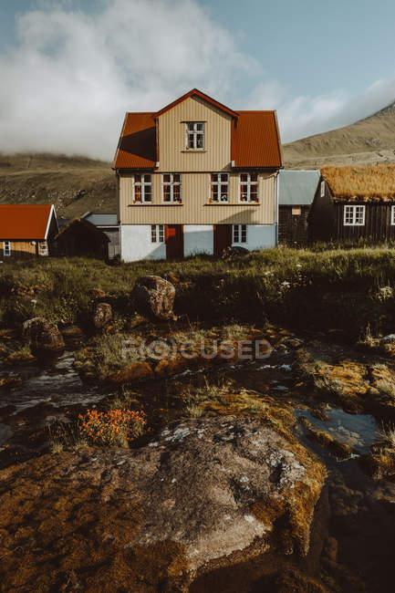 Accoglienti case di paese tradizionali sulle colline e sul fiume sull'isola di Feroe — Foto stock