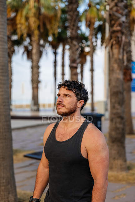Portrait of bearded active man in sportswear standing among palm trees — Stock Photo