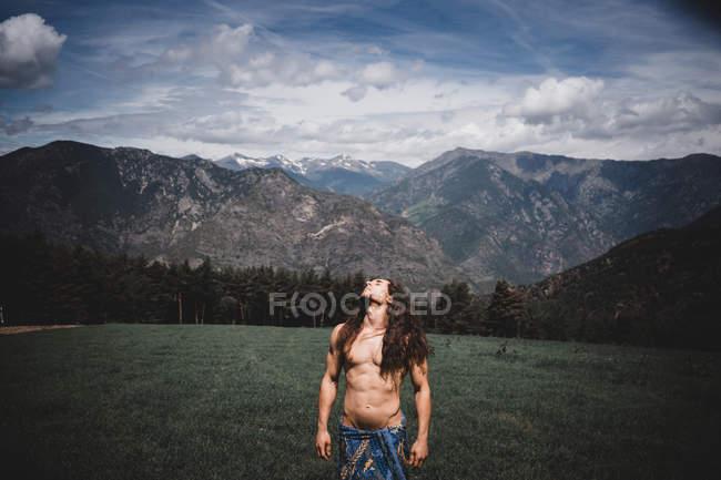 Привабливий безсоромний чоловік стоїть у прекрасній долині з горами під хмарним небом в Андоррі. — стокове фото