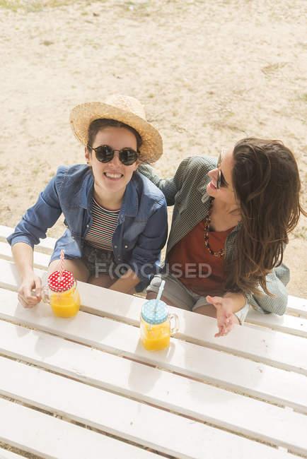 Des femmes souriantes s'amusent avec des bocaux avec du jus — Photo de stock