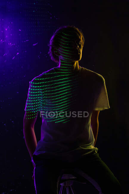 Unrecognizable young guy sitting on stool under green and violet illumination in dark room — Stock Photo