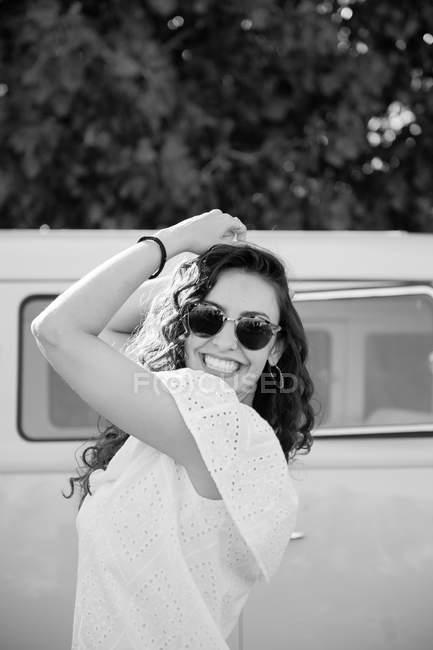 Jovem morena alegre posando perto de van — Fotografia de Stock