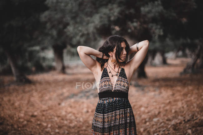 Woman in patterned dress touching hair and looking away while walking in amazing autumn forest in Mallorca, Spain — Stock Photo