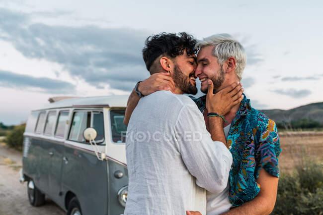 Боковой вид красивых молодых мужчин, обнимающих и целующихся, стоя в сельской местности рядом с ретро фургоном — стоковое фото