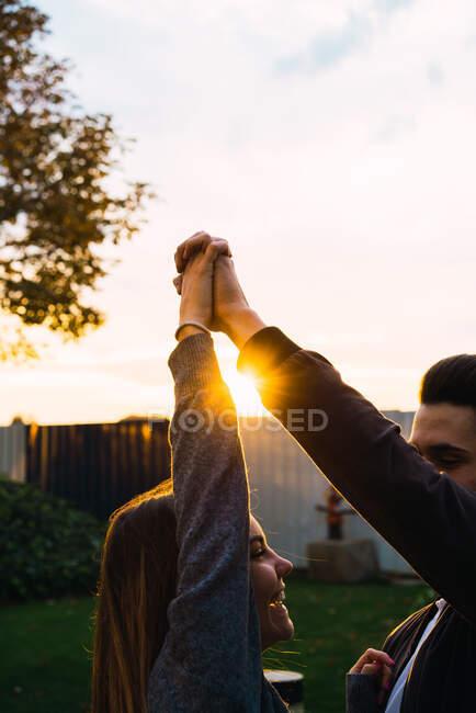 Молоді люди тримаються за руки, дивлячись один на одного під час заходу сонця.. — стокове фото