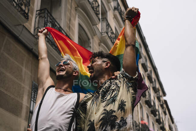 Пара мальчиков с флагом гей-гордости на улице Мадрида — стоковое фото