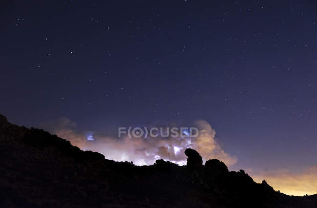 Rays and clouds in night storm over the mountain under a starry sky - foto de stock