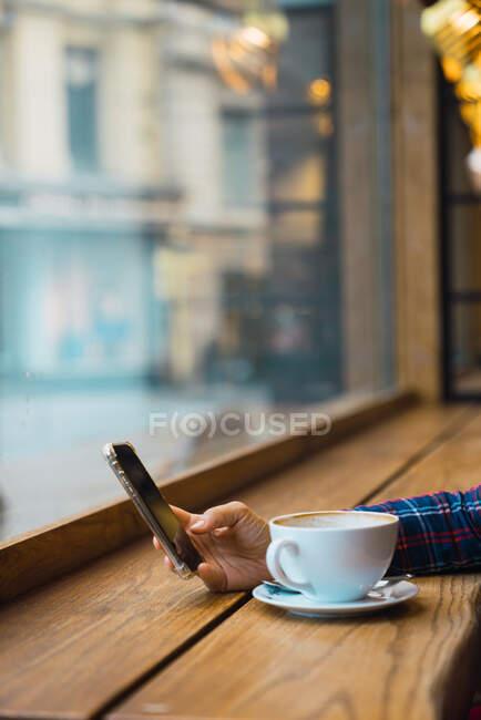Женщина сидит в кафе с чашкой кофе — стоковое фото