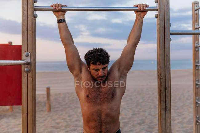 Muscular guy performing pull-ups on bar during sunset on sandy beach — Stock Photo
