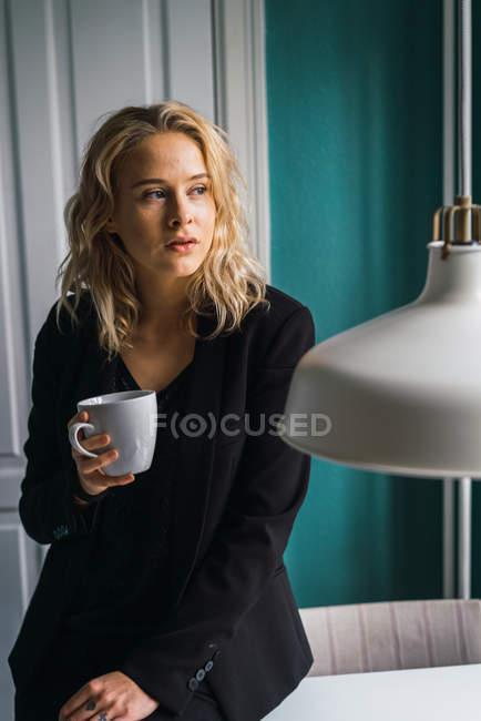 Романтичная женщина с Кубка, сидя у себя дома и глядя — стоковое фото