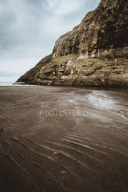 Beach and rocky cliff at calm ocean on Feroe Islands — Stock Photo