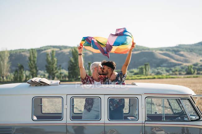 Два красивых мужчины целуются и держат яркий ЛГБТ-флаг, стоя внутри фургона с открытой крышей в сельской местности в солнечный день — стоковое фото