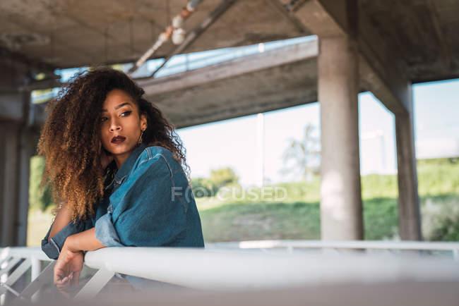 Giovane donna in camicia di jeans in piedi sul balcone vicino ringhiera e guardando altrove — Foto stock